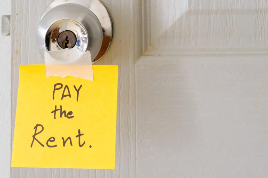 Sticky note saying Pay your rent on doorknow