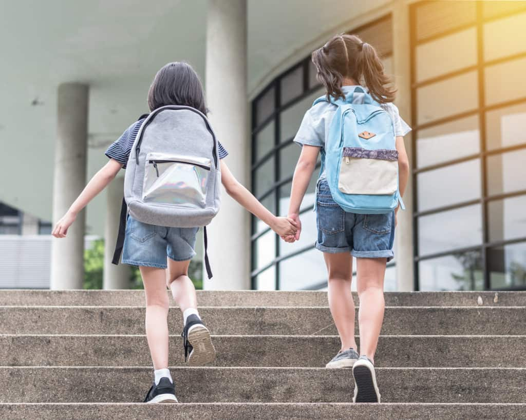 Two schoolkids walking up stairs