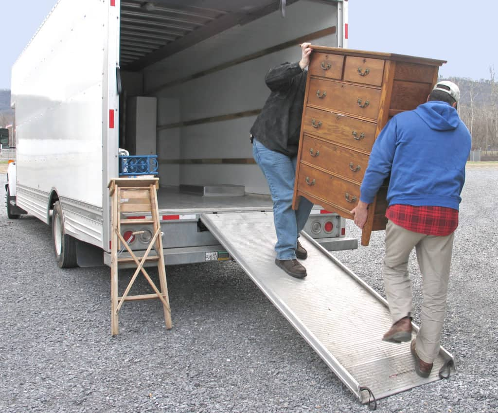 Two movers carrying a dresser into a moving truck